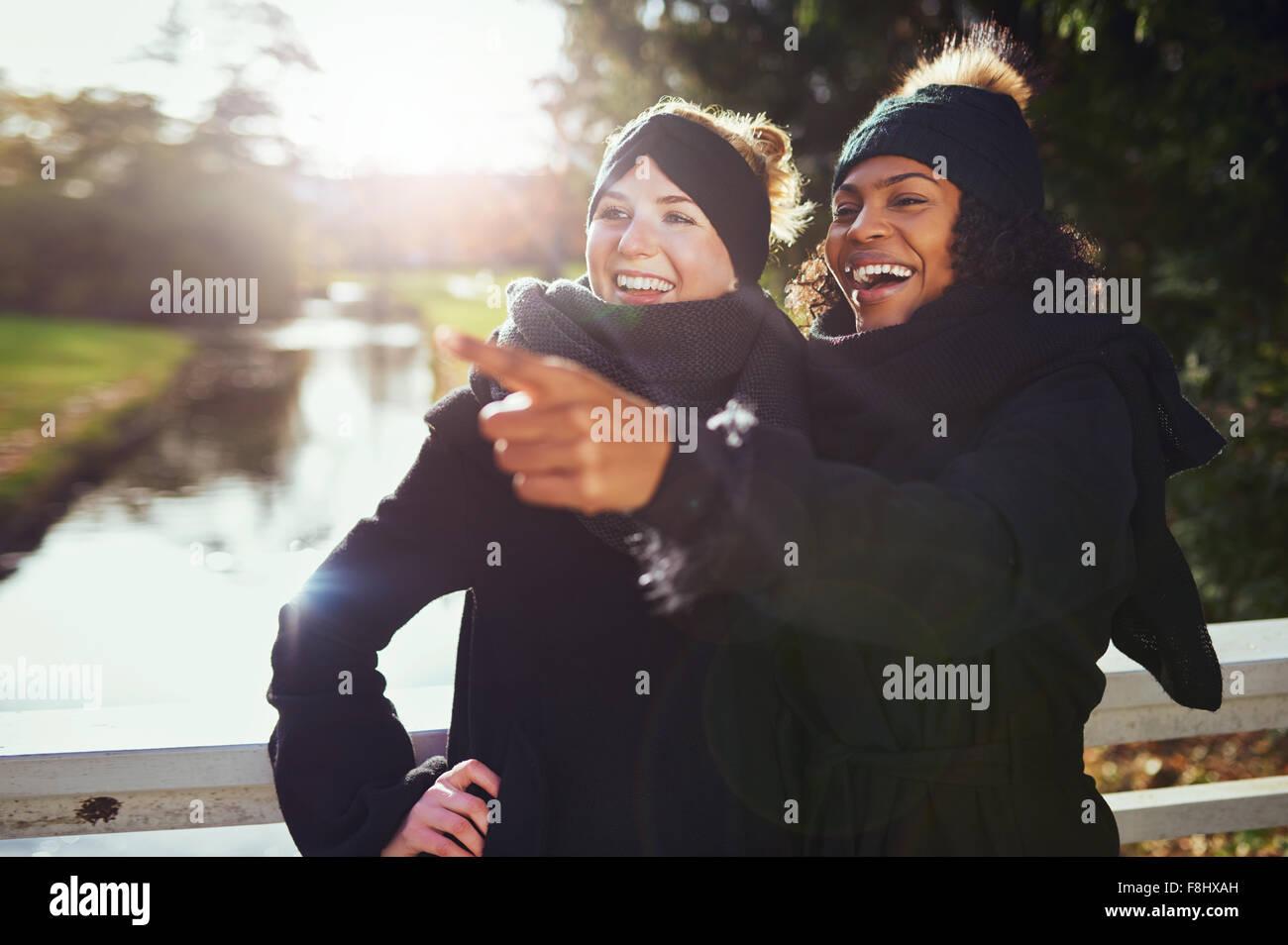 Zwei Freundinnen lachend an etwas beim Stehen in der Park gegen des Flusses. Stockbild