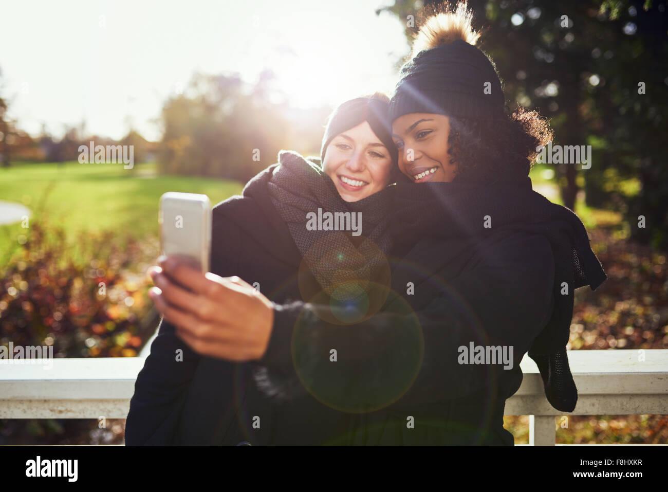 Zwei lächelnde junge Frauen, die vor der herbstlichen Park selfie Stockbild