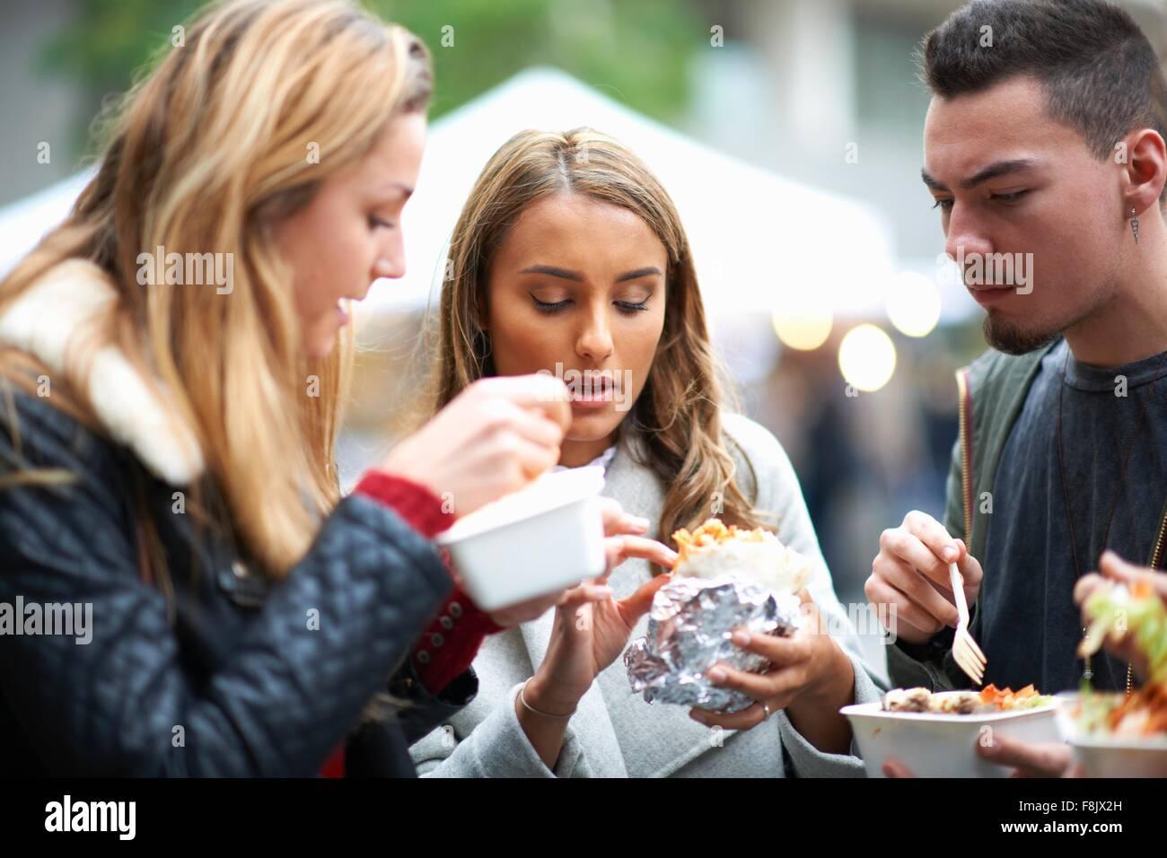 Gruppe junger Erwachsener, Speisen zum mitnehmen, im Freien zu essen Stockbild