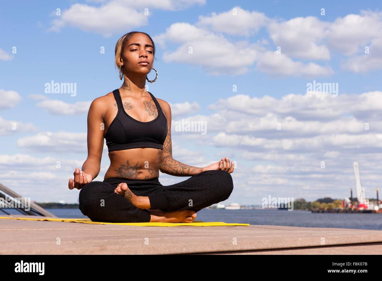 Junge Frau sitzt Schneidersitz durch Wasser in Yogaposition, Augen geschlossen, Philadelphia, Pennsylvania, USA Stockbild