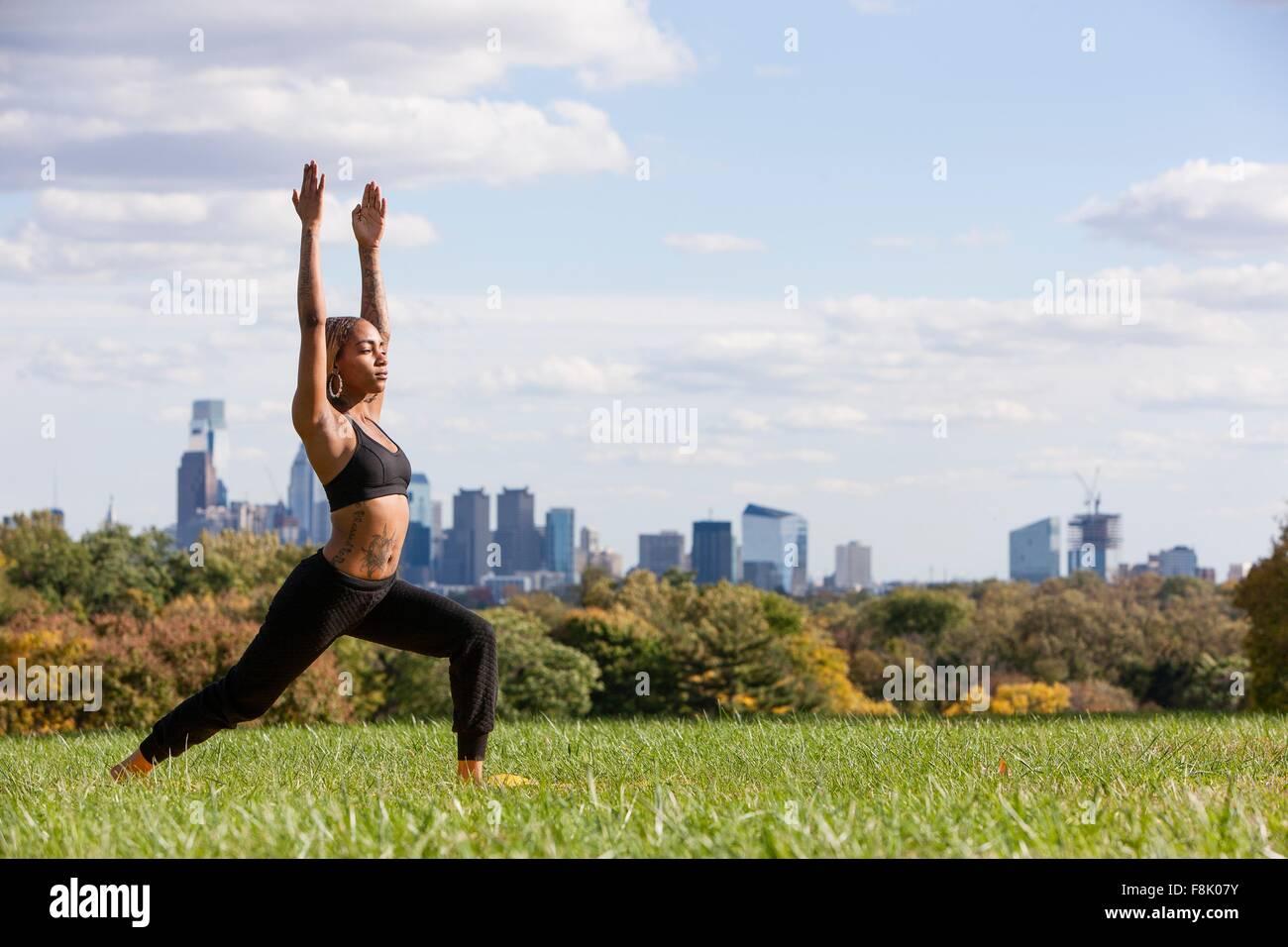 Seitenansicht der jungen Frau auf dem Rasen in Yogaposition, Arme angehoben, Augen geschlossen, Philadelphia, Pennsylvania, Stockbild