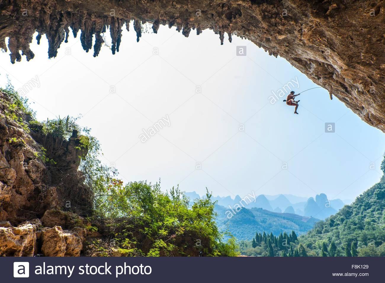 Männliche Bergsteiger unter einem Sturz an Den Odin neben Moon Hill in Yangshuo, Guangxi Zhuang, China Stockbild