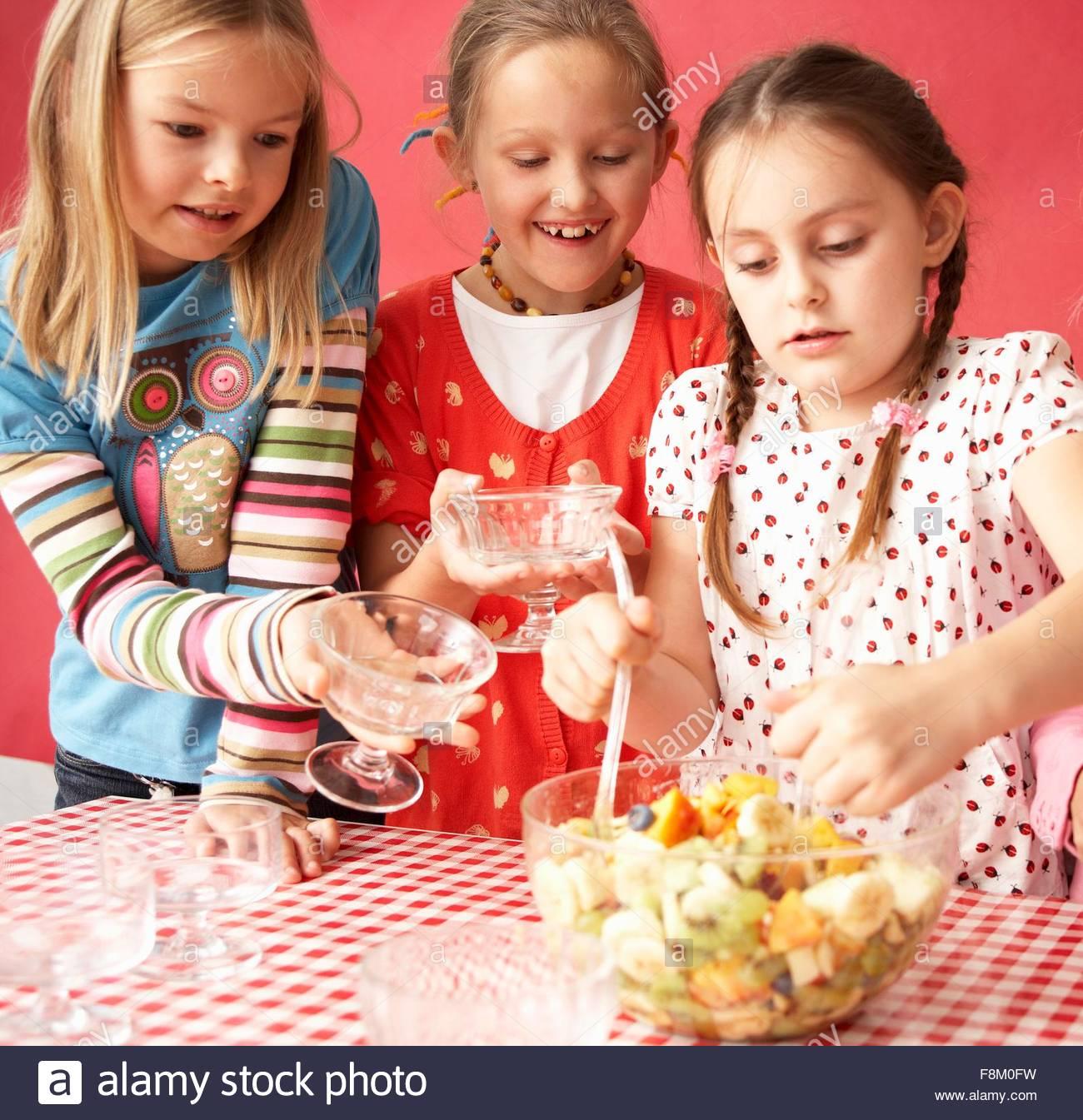 Drei Mädchen essen Obstsalat Stockbild