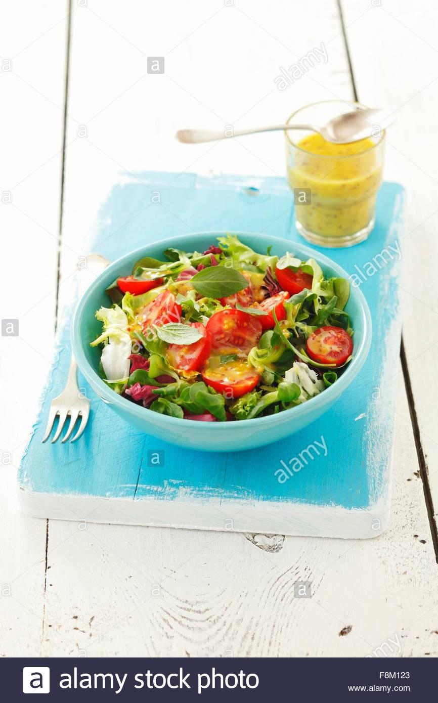 Salatblätter mit Cherry-Tomaten und Honig & Senf-dressing Stockbild