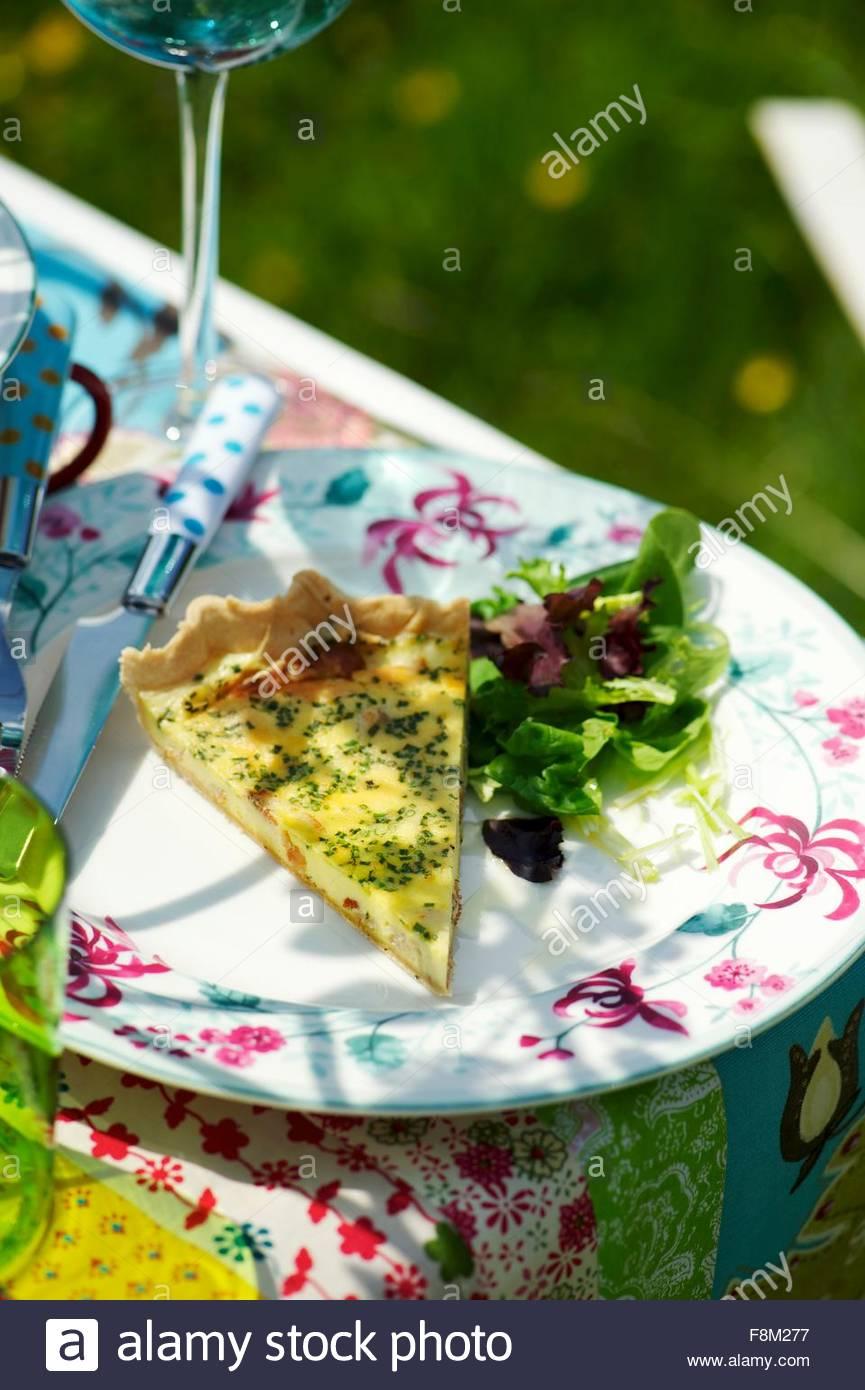 Ein Stück Käse Quiche mit einem gemischten Blattsalat auf einem Gartentisch Stockbild