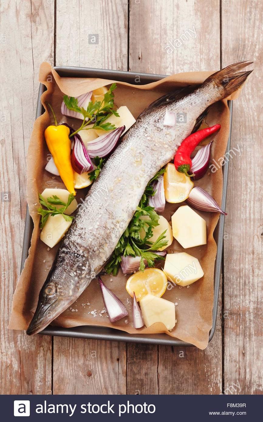 Seehecht mit Gemüse, Zitronen und Petersilie auf ein Backblech Stockbild