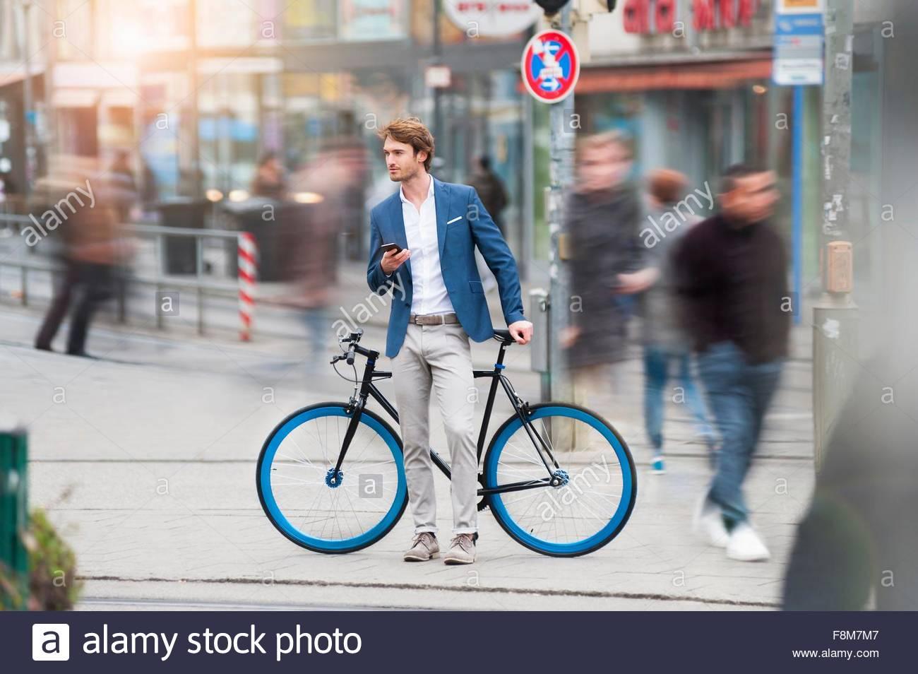 Differenzielle Fokus der junge Mann mit Fahrrad in belebten Straße halten Handy wegschauen Stockbild