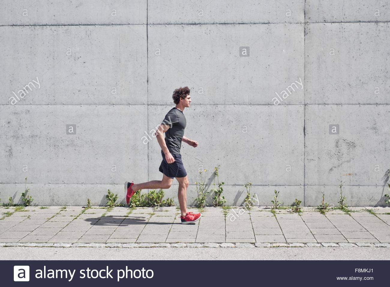 Junger Mann auf städtischen Bürgersteig entlang laufen Stockbild