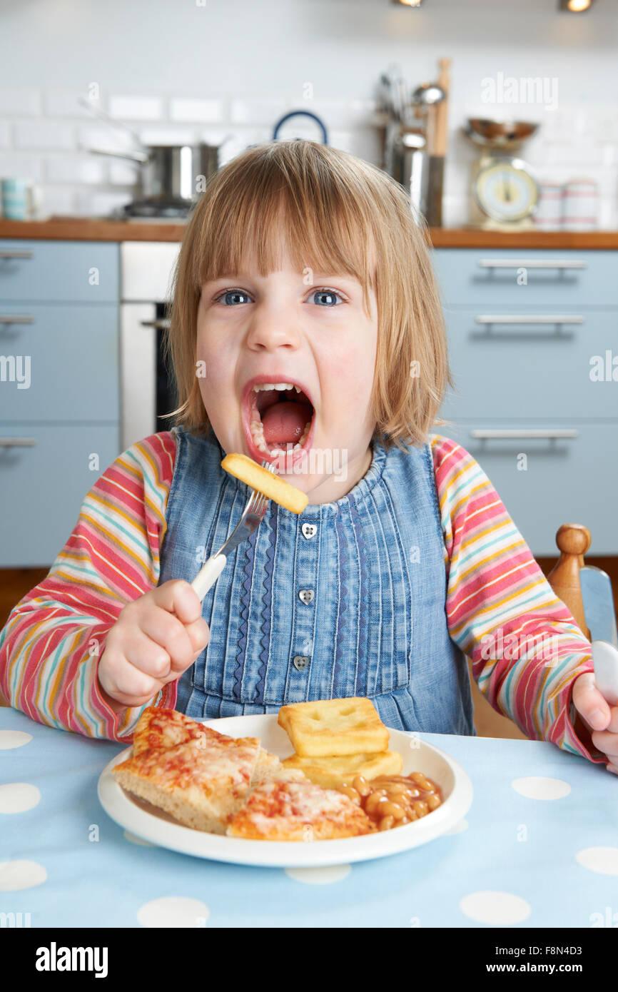 Junge Mädchen, die ungesunde Mittagessen genießen Stockbild