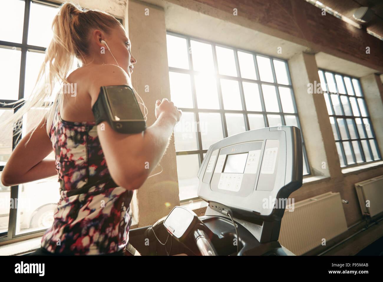 Young konzentrierte sich weibliche trainieren Sie im Fitnessstudio auf dem Laufband Joggen. Fitness-Frau laufen Stockbild