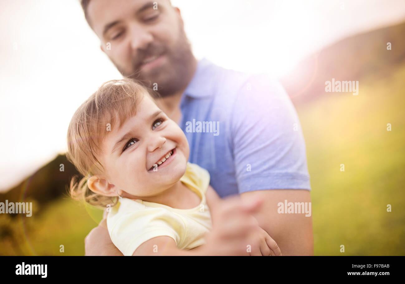 Hipster-Vater mit seiner kleinen Tochter in den grünen Park zu spielen. Stockbild