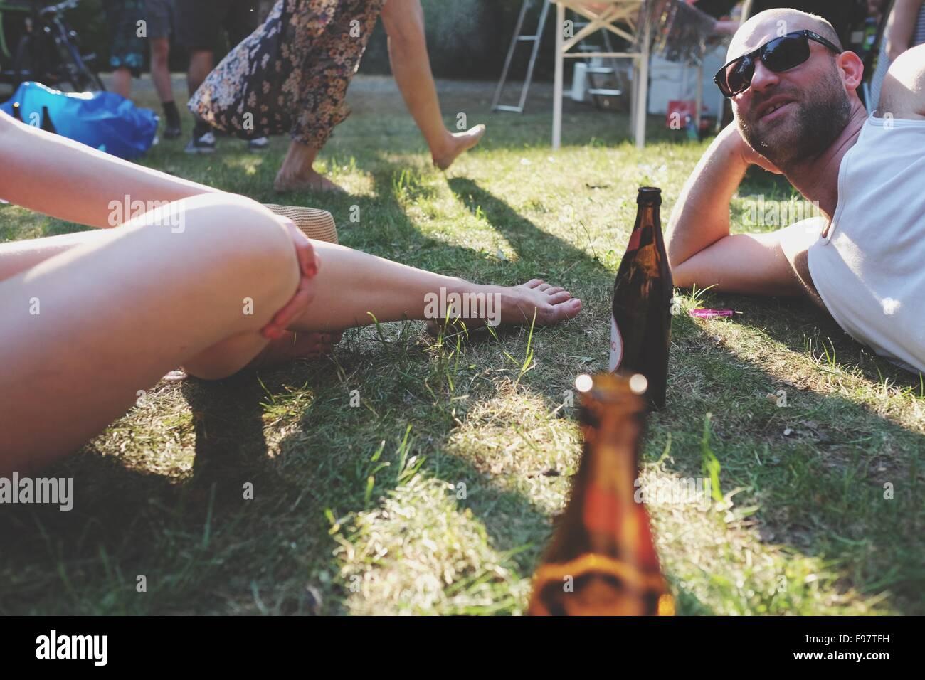 Mann und Frau mit Bierflaschen im Park Stockbild