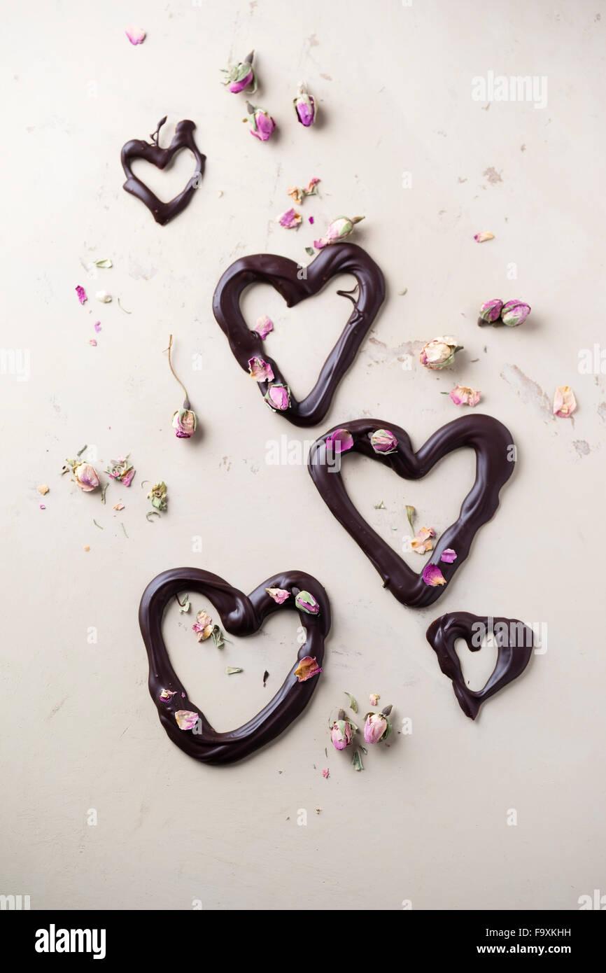 Schokoladenherzen und getrockneten Rosenblüten auf hellem Grund Stockbild