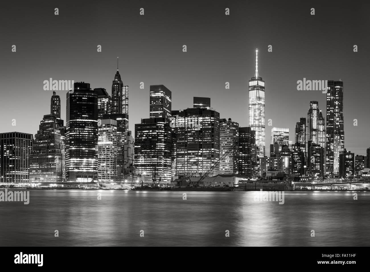& Schwarz-weiß East River Sicht auf Financial District in der Abenddämmerung. Beleuchtete Skyline Stockbild