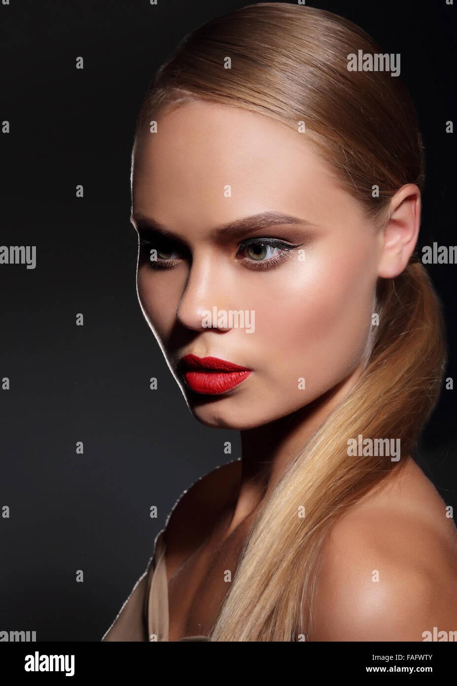 Junge Frau mit glattem Haar und und rote Lippen auf dunklem Hintergrund. Porträt. Stockbild