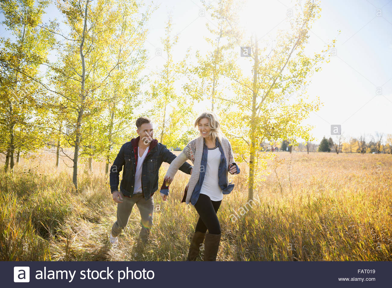 Paar im sonnigen Feld laufen Stockbild