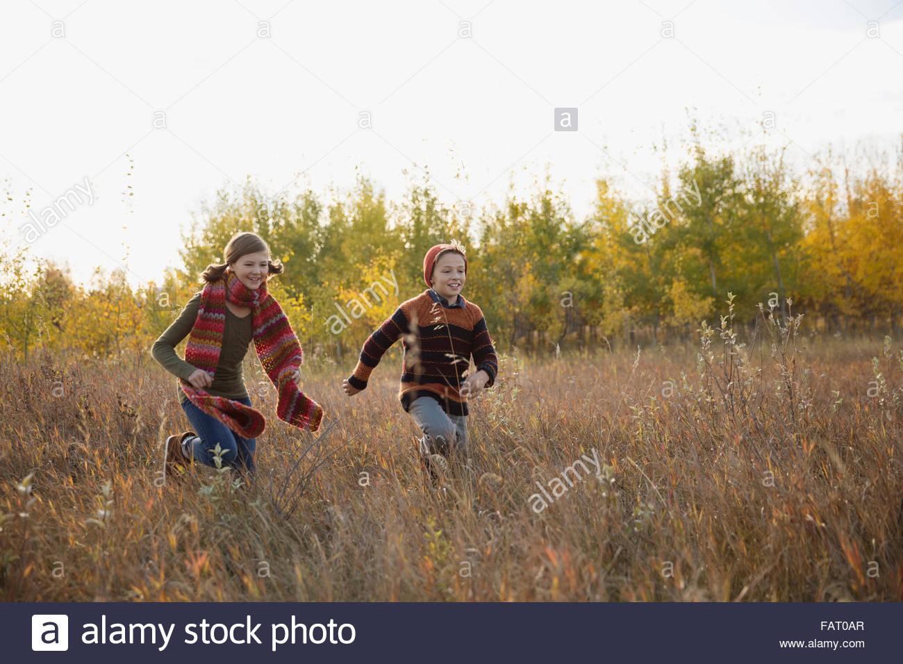 Bruder und Schwester im Herbst Feld laufen Stockbild