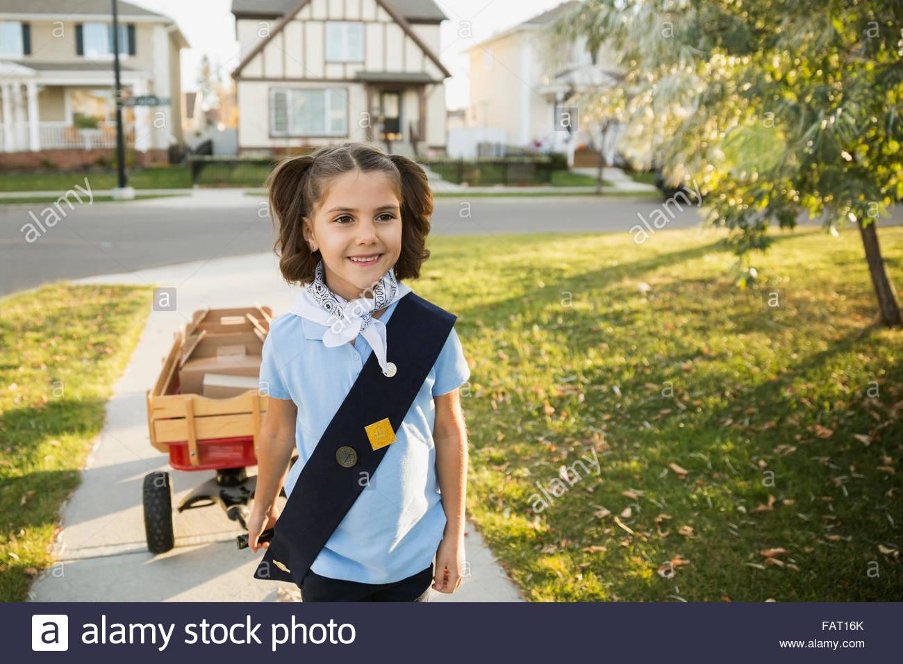 Lächelnde Pfadfinderin mit Wagen verkaufen Cookies Nachbarschaft Stockbild