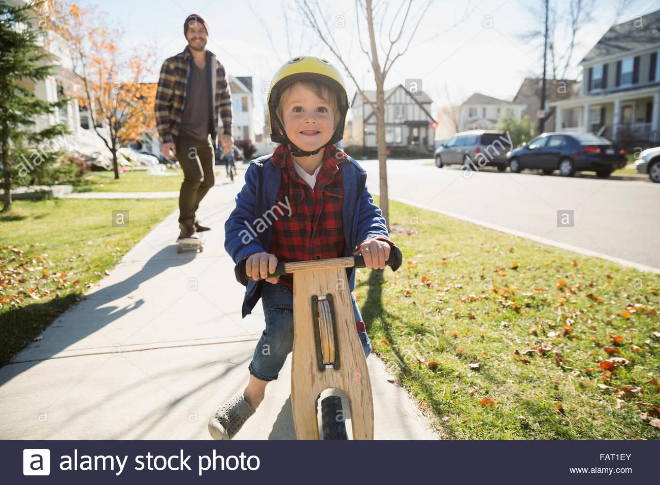 Lächelnde junge Reiten Push Scooter auf Nachbarschaft Bürgersteig Stockbild