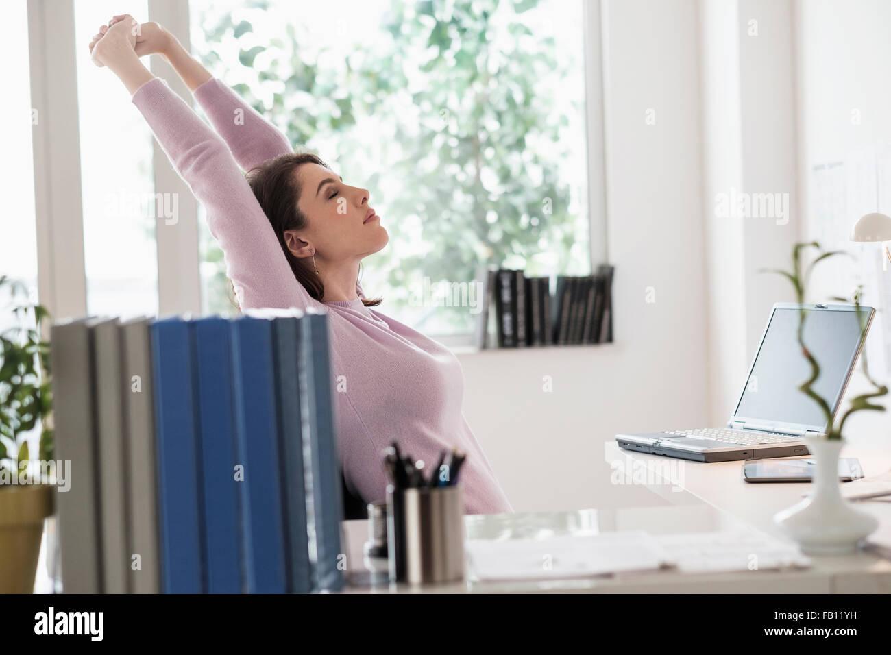 Junge Frau erstreckt sich vom Schreibtisch Stockbild