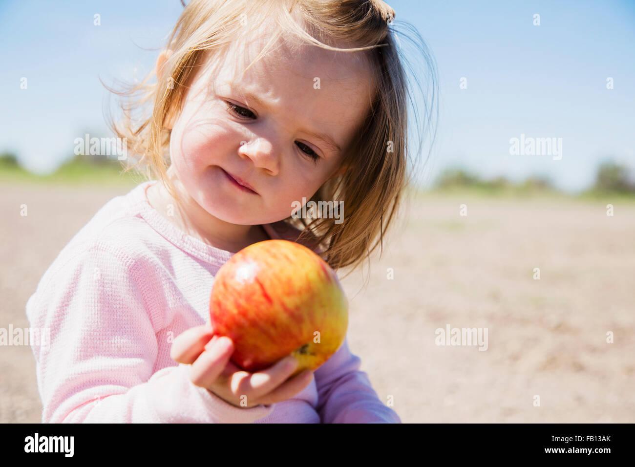 Porträt von Mädchen (2-3) Holding apple Stockbild