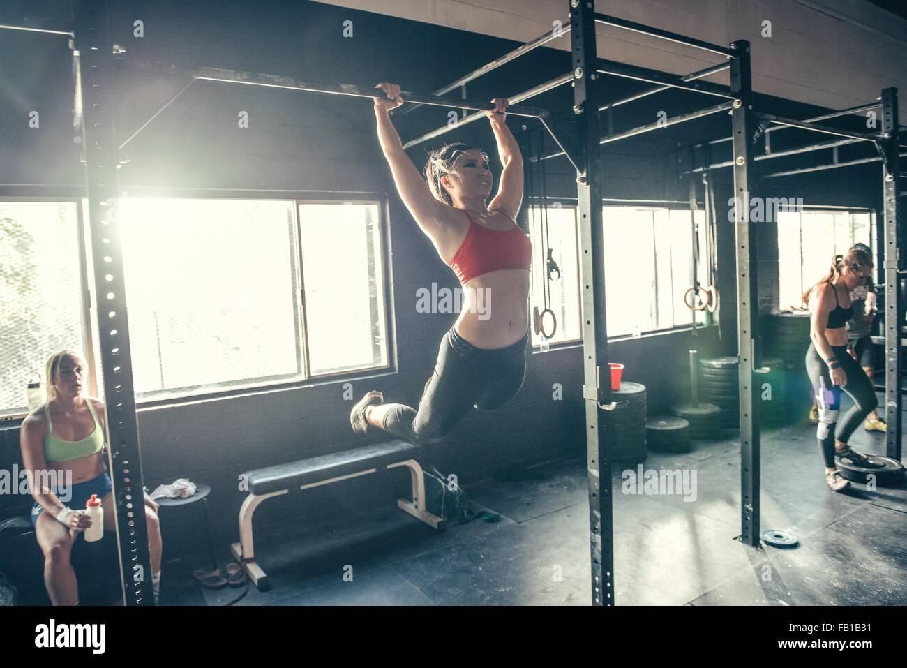 Frau schwingen auf Übung Bar im Fitness-Studio Stockbild