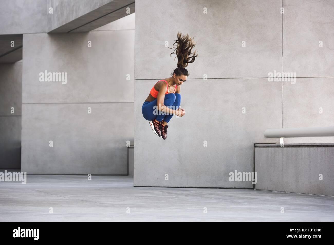 Seitenansicht der jungen Frau umarmt Knie in der Luft springen Stockbild