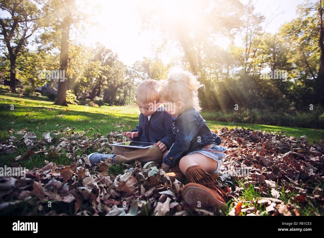 Kinder sitzen auf Herbst Blatt bedeckt Rasen blickte mit digital-Tablette Stockbild