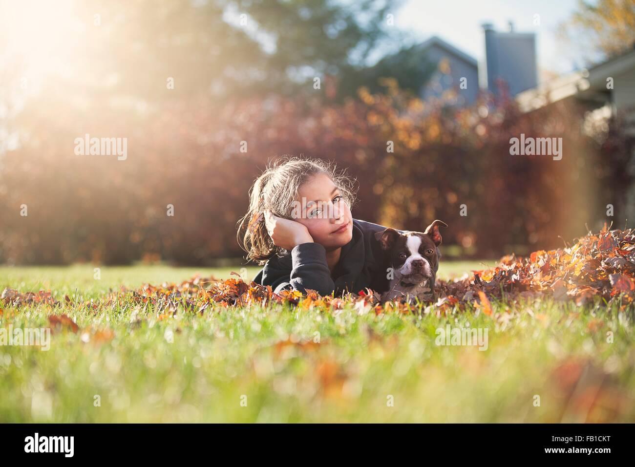 Mädchen mit Boston Terrier Welpe liegend vorne auf Herbstblatt bedeckt Rasen, ruht auf Ellenbogen Blick in Stockbild