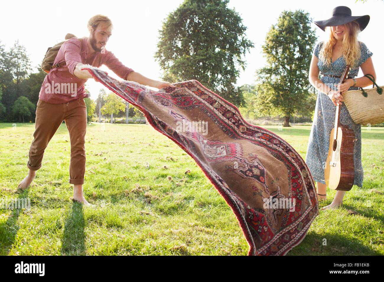 Romantische junges Paar ausbreitenden Teppich für Picknick im park Stockbild