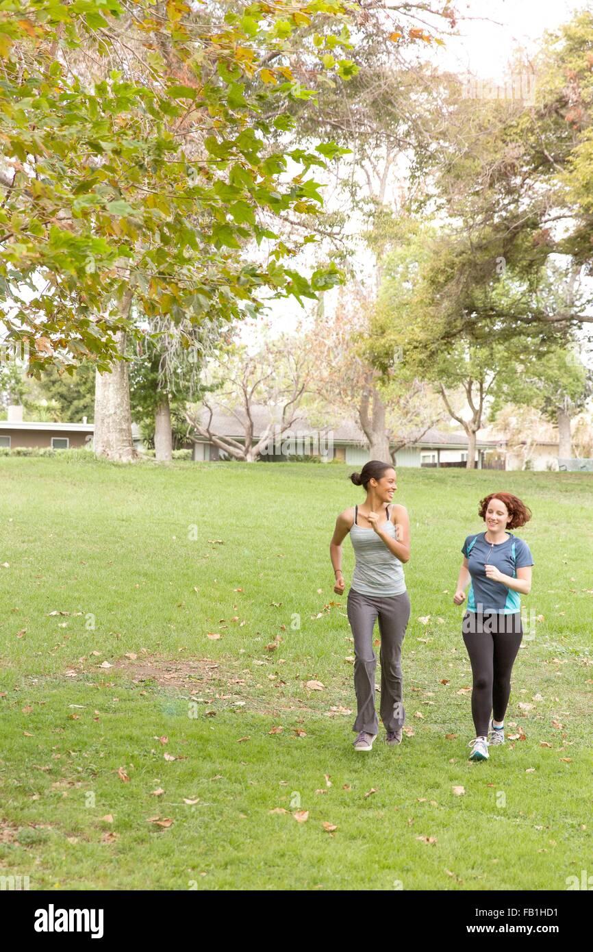 Voller Länge Vorderansicht der Trägerinnen Sportbekleidung laufen auf dem Rasen Stockbild