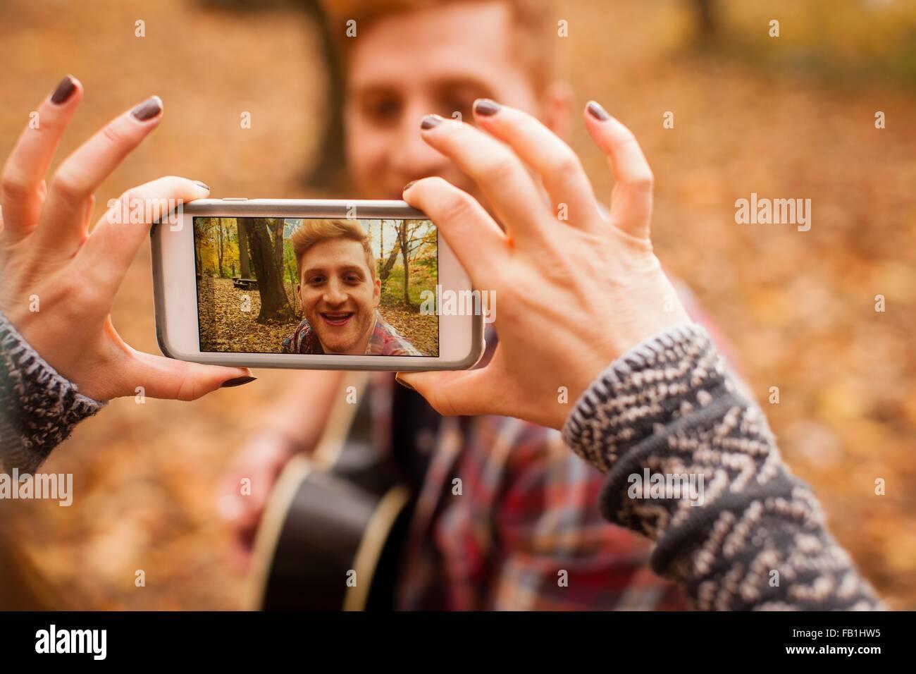 Hände der jungen Frau fotografieren Freund auf Smartphone im herbstlichen Wald Stockbild