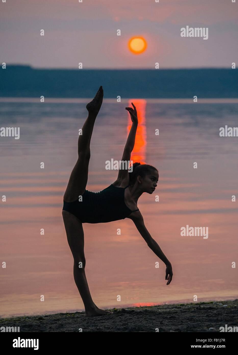 Mädchen, Meer bei Sonnenuntergang auf einem Bein, biegen nach vorne Arm und Bein angehoben Stockbild