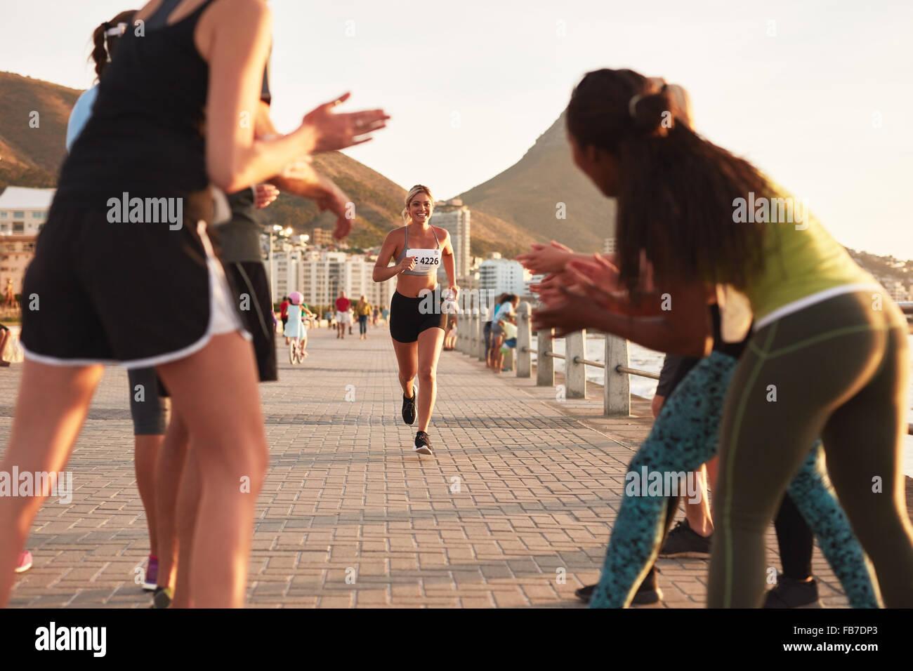 Glückliche junge Sportlerin wird von Anhängern applaudierten, als sie die Ziellinie eines laufenden Rennens Stockbild
