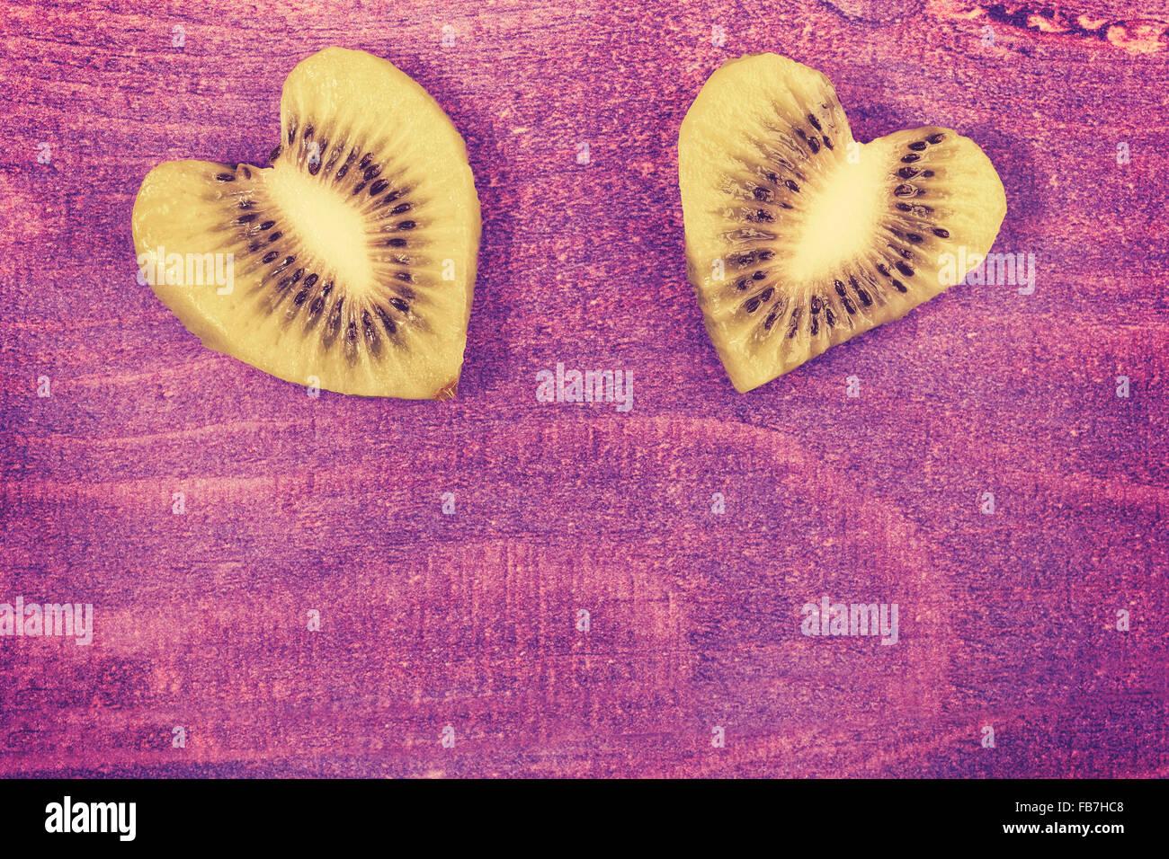 Vintage getönten Herz aus Kiwi auf hölzernen Hintergrund, Platz für Text. Stockbild