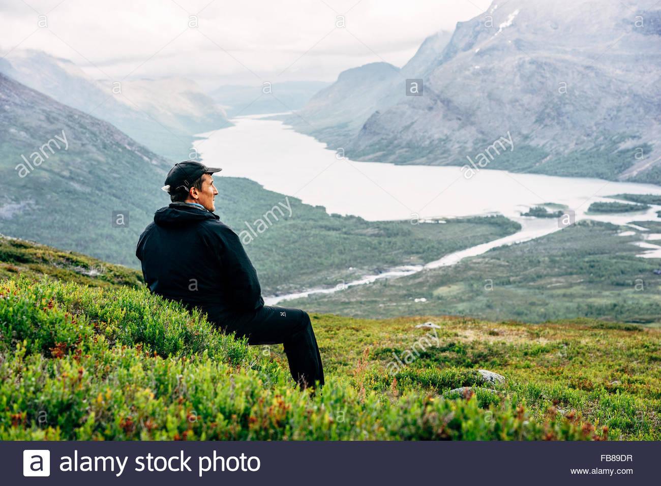 Schweden, Lappland, Kaitumjaure, Kungsleden, männliche Wanderer sitzen und mit Blick auf den Fluss im Tal Stockbild