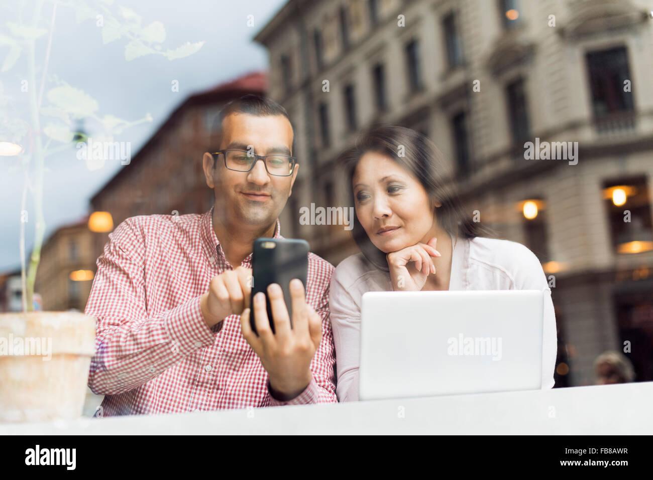 Schweden, Uppland, Stockholm, Mann und Frau mit Smartphone im café Stockbild