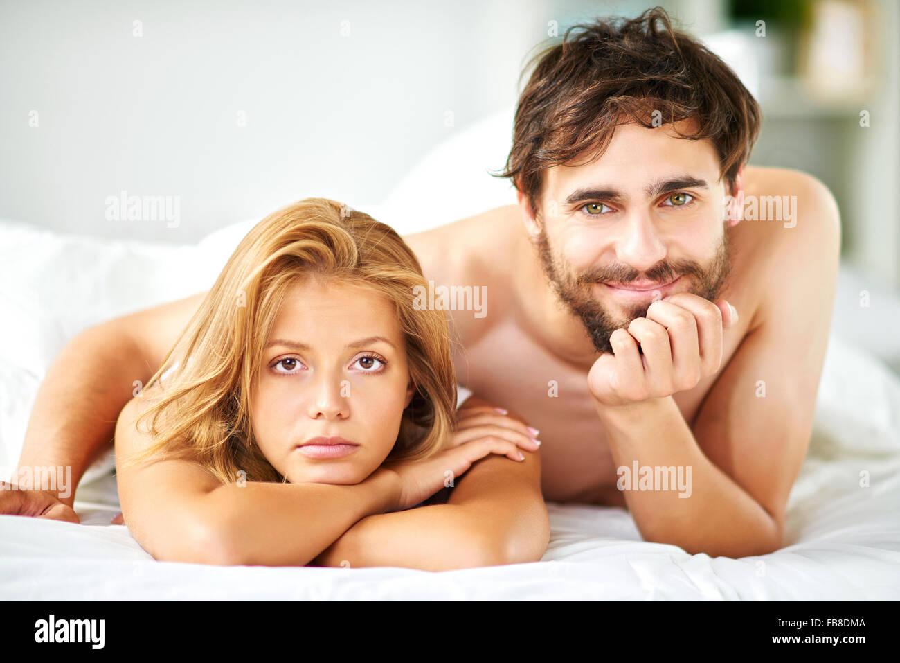 Junges Paar Blick in die Kamera beim liegen im Bett Stockbild