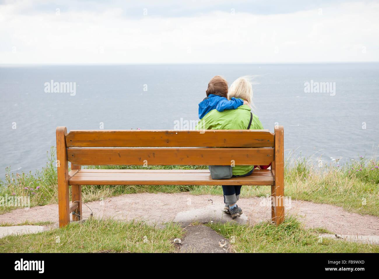 Schweden, Skane, Kullaberg, Kullen, Mutter und Sohn (8-9) sitzen am Strand und am Meer suchen Stockbild