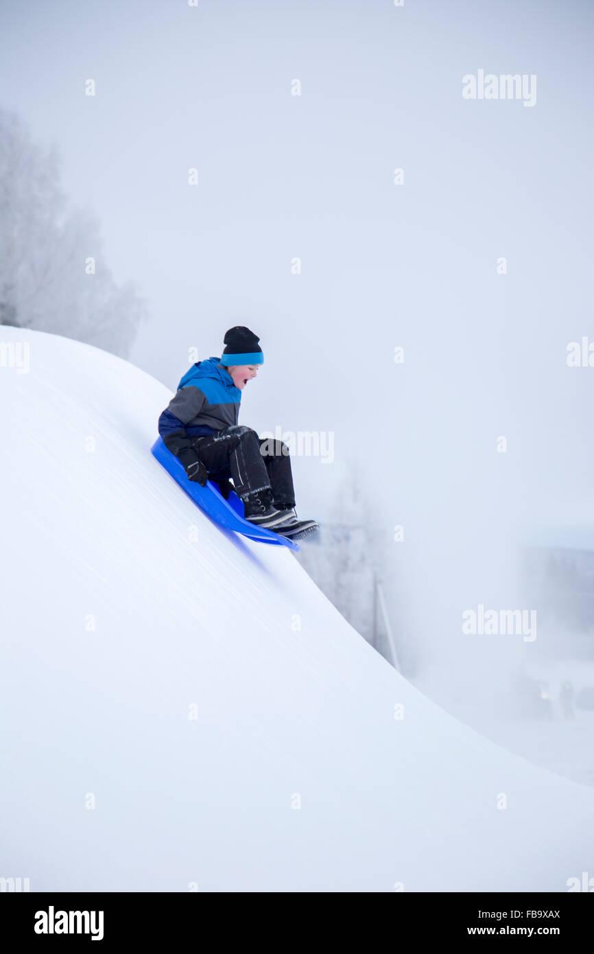 Schweden, Värmland, Sunne, Boy (12-13) verschneiten Berg hinunter rodeln Stockbild