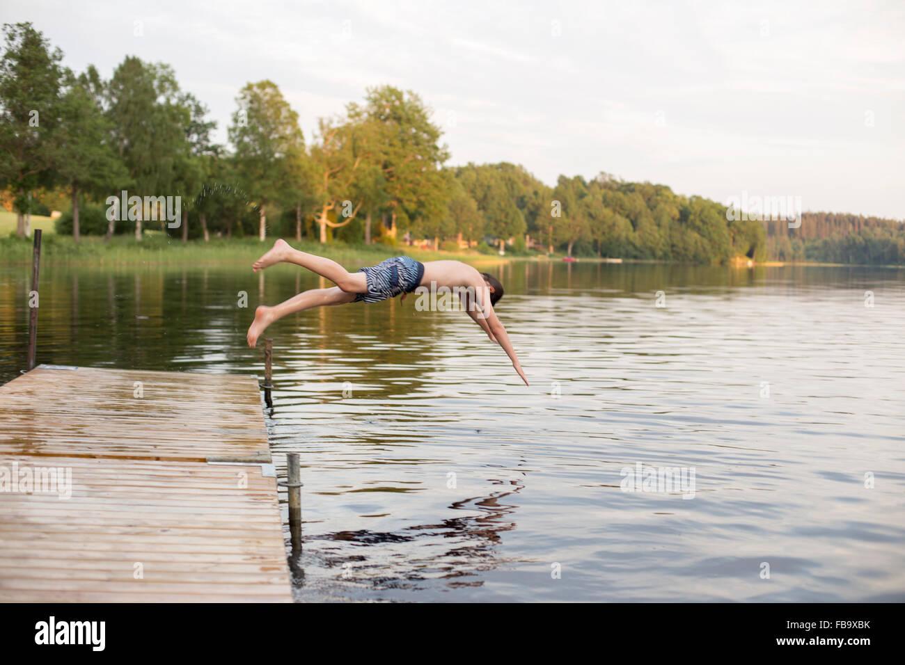 Schweden, Smaland, Braarpasjon, Boy (12-13) von der Anlegestelle in See springen Stockbild