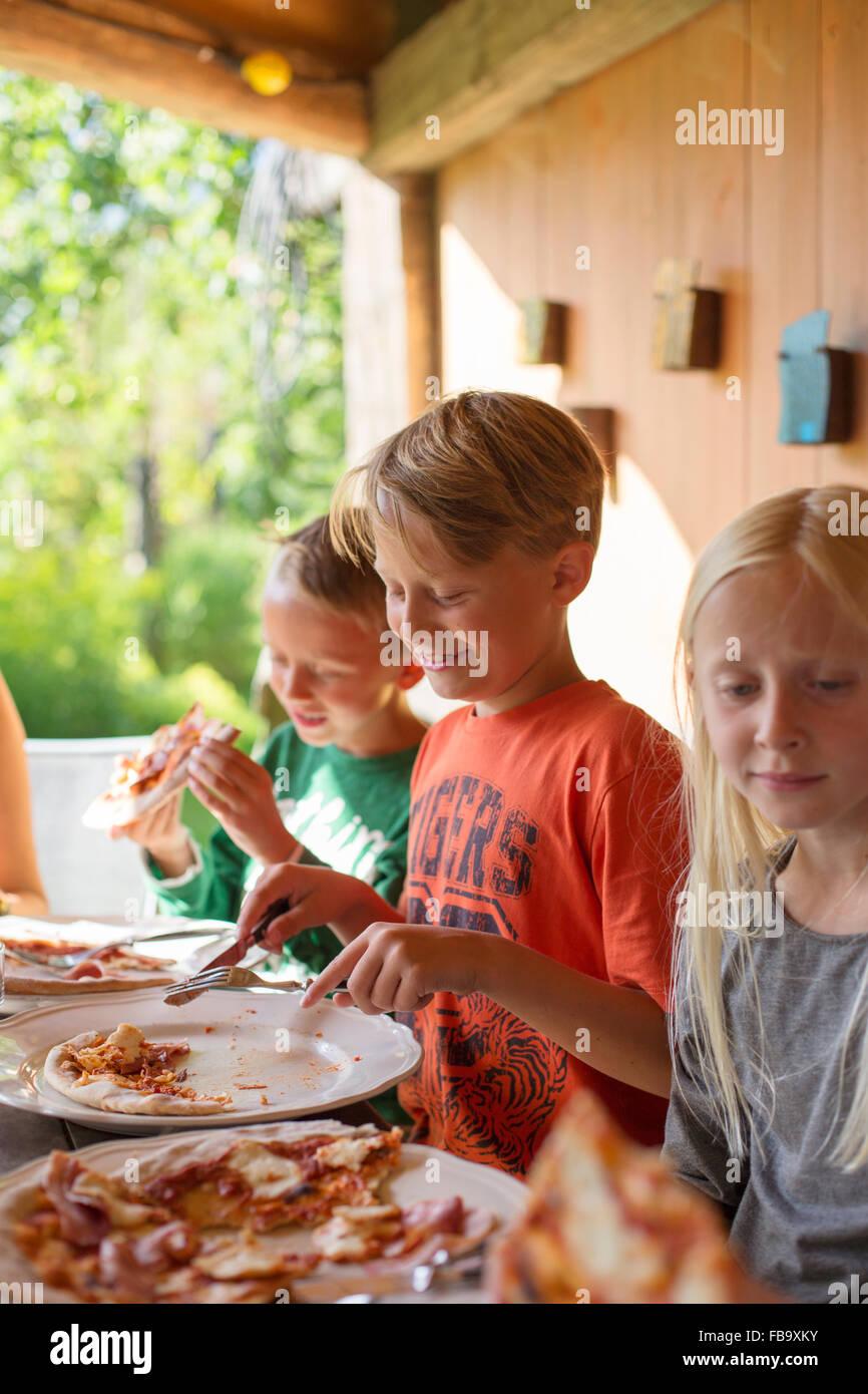 Schweden, Skane, Brüder (8-9) und Schwester (10-11) Essen Pizza bei Familienessen Stockbild