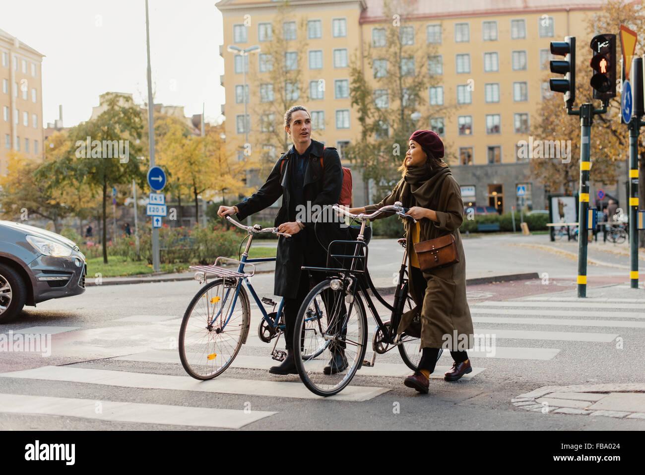 Schweden, Uppland, Stockholm, Vasastan, Vanadisplan, zwei Jugendliche mit Fahrrädern zu Fuß durch Zebrastreifen Stockbild