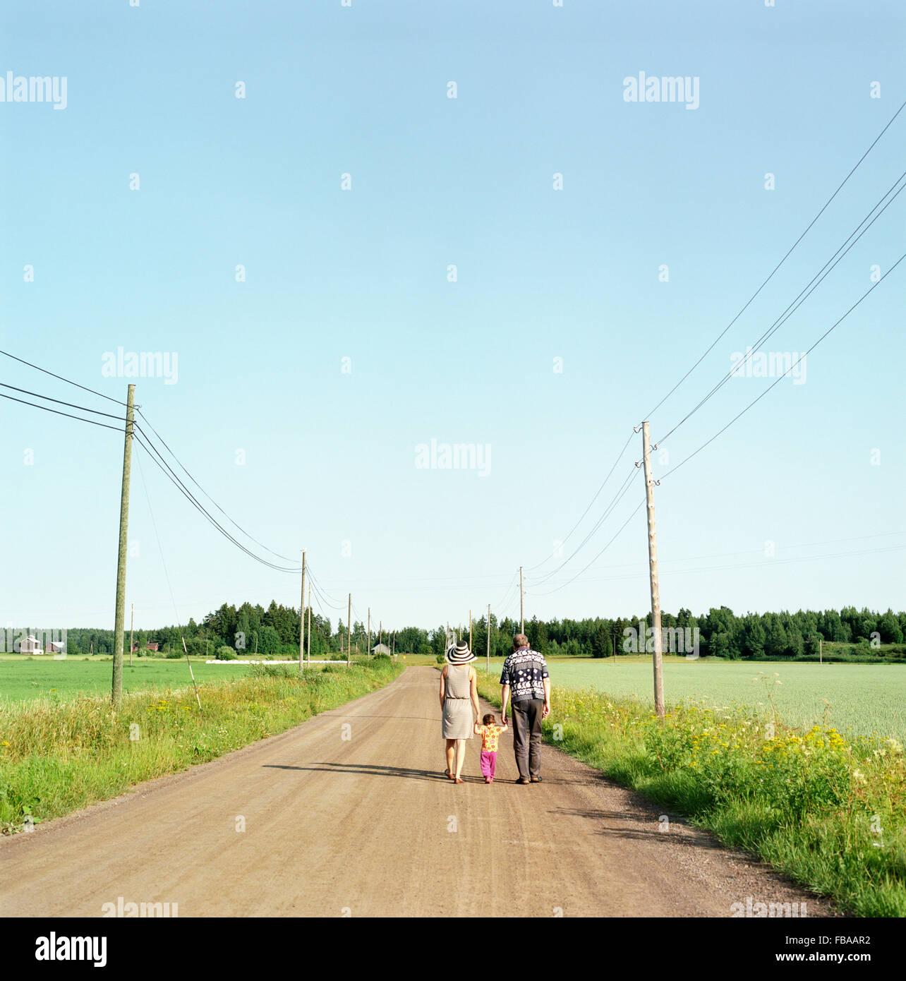 Finnland, Uusimaa, Lapinjarvi, Rückansicht von Personen mit Kind (2-3) Feldweg entlang Stockbild