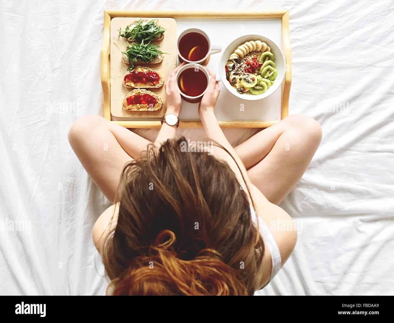 Direkt über Bild der Frau im Bett zu frühstücken Stockbild