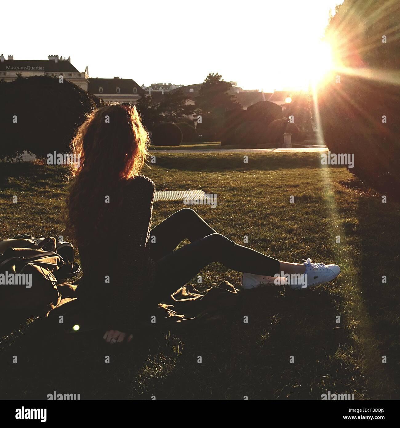 Frau sitzt auf Wiese In sonniger Tag Stockbild