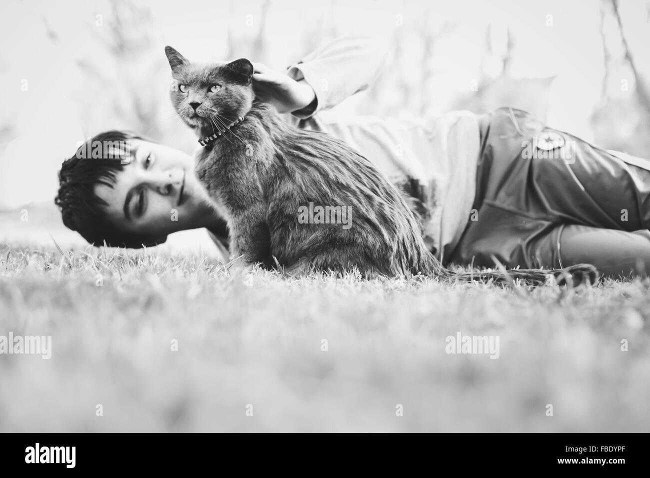 Junge liegend auf Wiese mit Katze Stockbild
