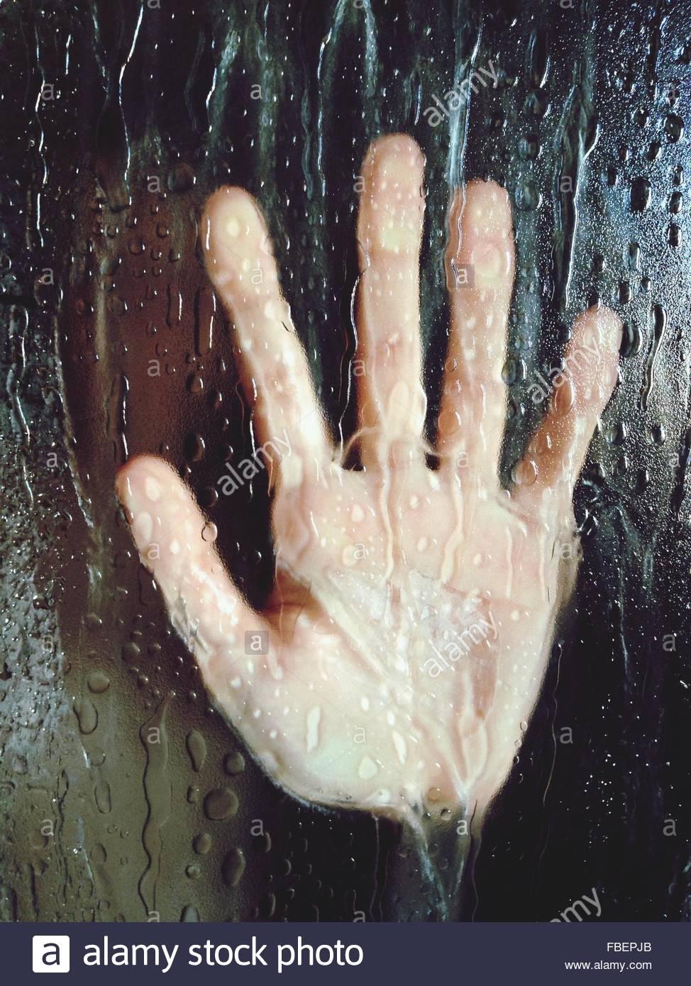 Nahaufnahme der Hand auf nassen Glas Stockbild