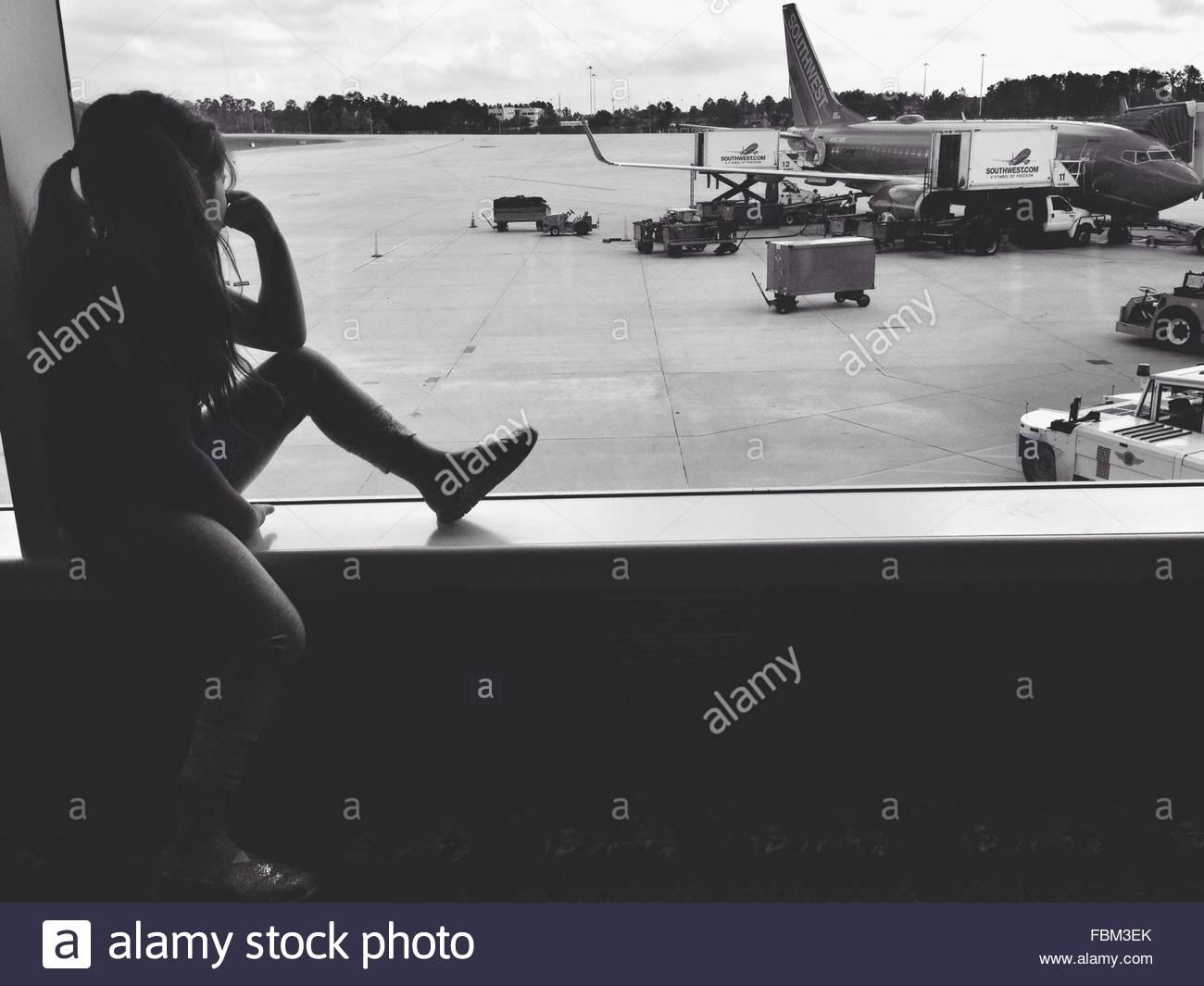 Kleines Mädchen sitzt auf der Fensterbank am Flughafen Stockbild