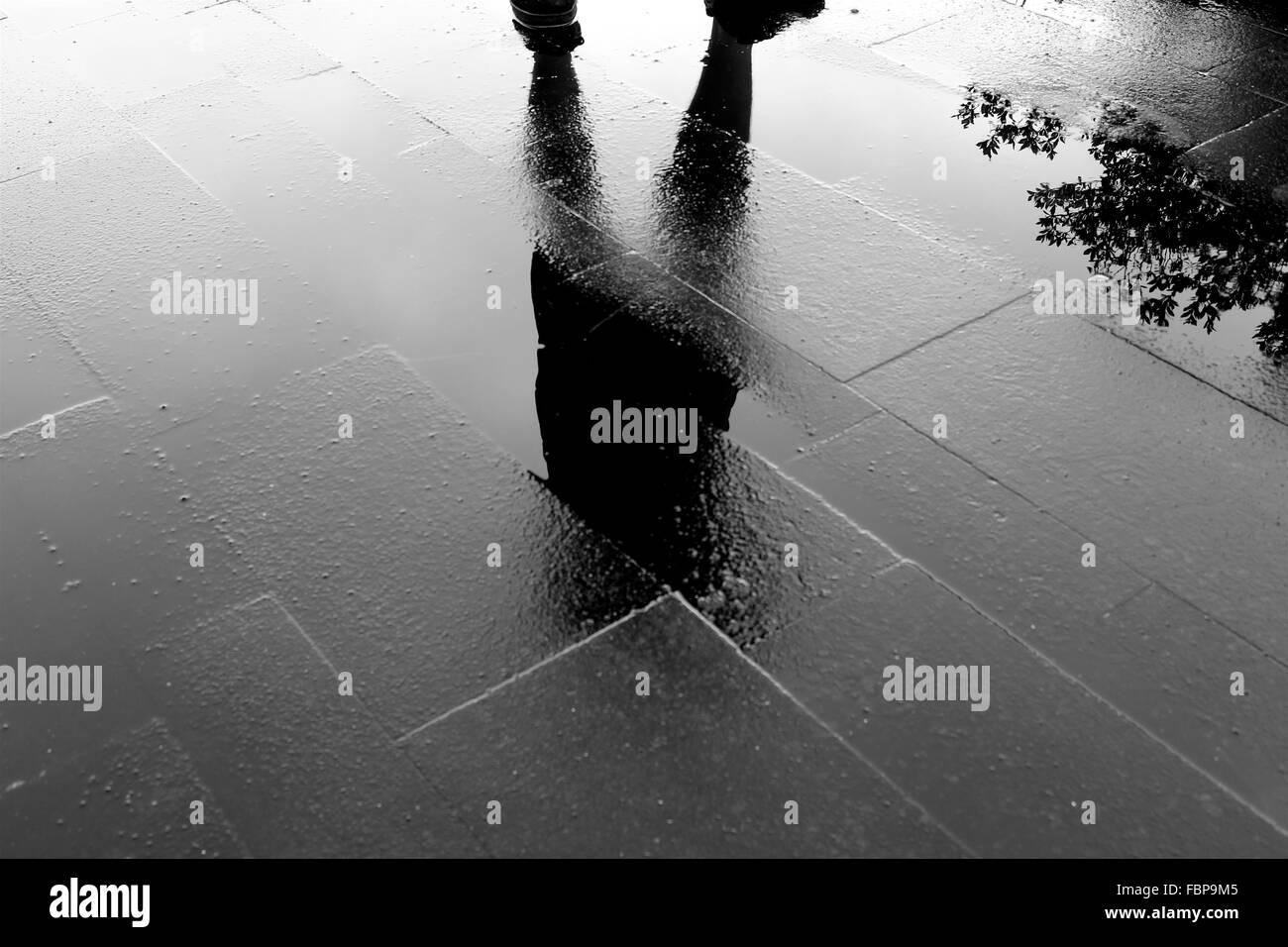 Reflexion des Menschen In Pfütze Stockbild
